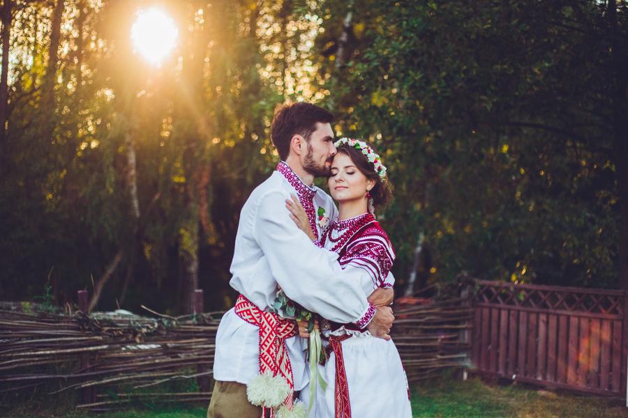 Молодожены обнимаются в белорусских национальных костюмах