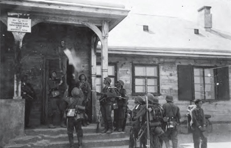Гитлеровцы сбивают звезду со здания Тришинской школы в Бресте